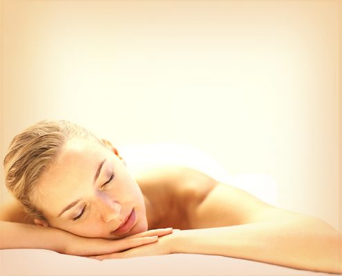 Portrait of a pretty relaxed female with eyes closed at a spa treatment with lots of copyspace