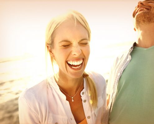 Closeup of a joyful young couple laughing on the beach