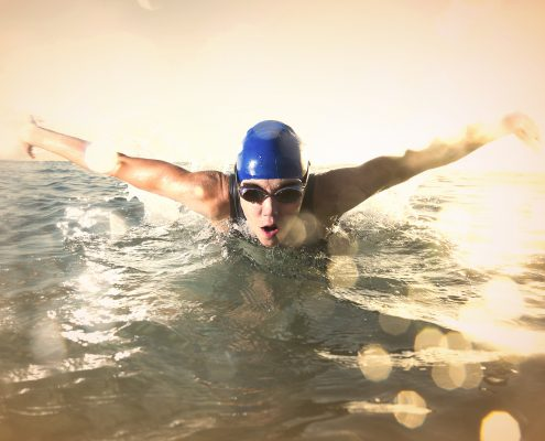 Female butterfly stroke swimmer, captured moment